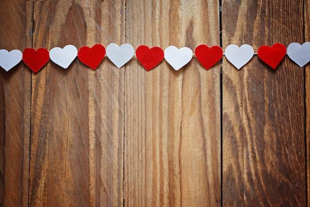 Coeurs de papier rouge et blanc sur la corde à linge sur bois backgrou