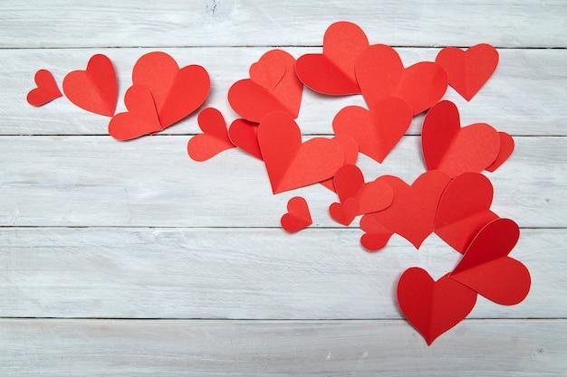 Coeurs de papier rouge sur bois blanc saint valentin