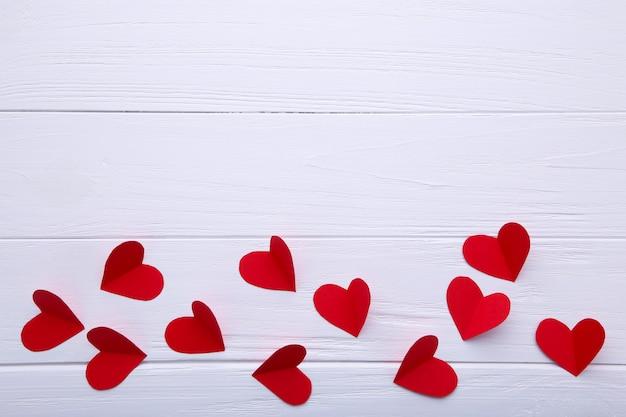 Coeurs de papier rouge sur fond blanc.