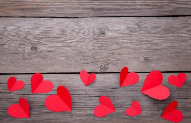 Coeurs de papier rouge sur fond gris.