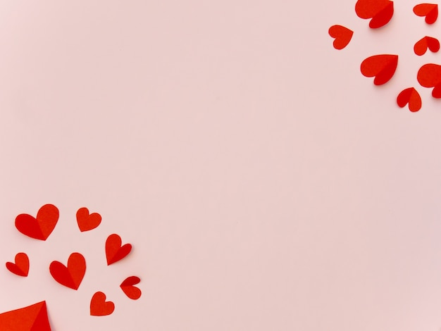 Coeurs de papier rouge sur fond rose avec un espace pour votre texte.