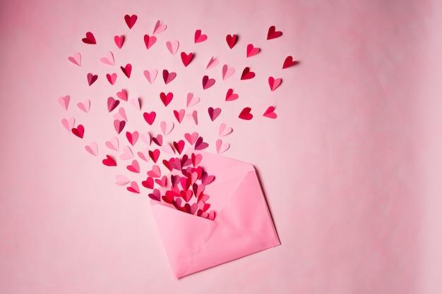 Coeurs de papier rouge et rose dans une enveloppe postale rose ouverte sur rose