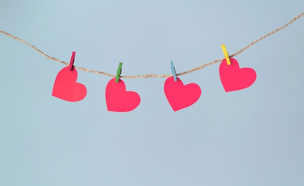 Des coeurs en papier sont accrochés à des pinces à linge sur une corde sur un fond bleu pastel. concept de la saint-valentin.