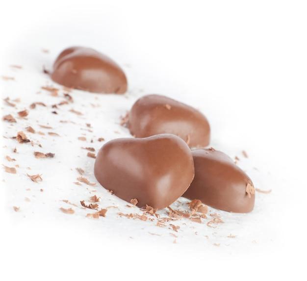 Coeurs et pépites de chocolat sur un blanc.