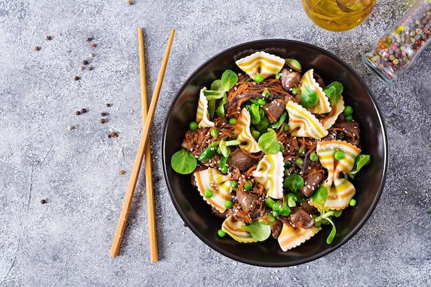 Coeurs de poulet aux carottes à la sauce aigre-douce avec des pâtes farfalle. lay plat.