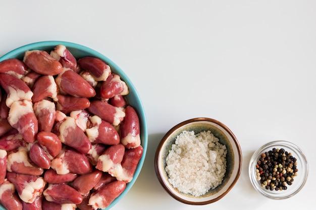 Coeurs de poulet cru frais et épices sur tableau blanc