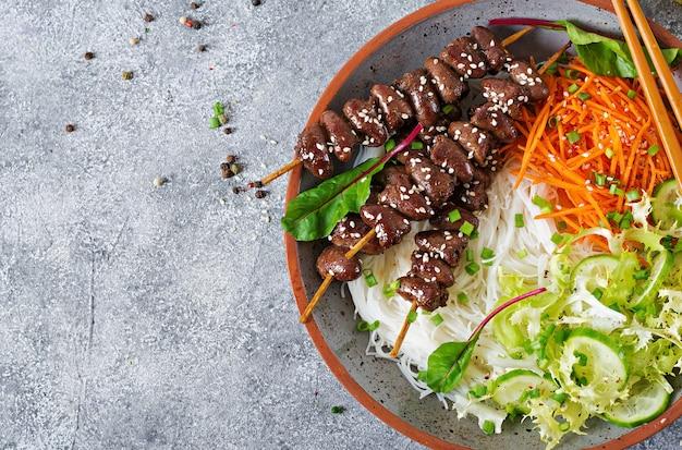 Coeurs de poulet à la sauce épicée, nouilles et salade de légumes. la nourriture saine. vue de dessus