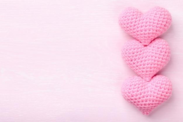 Coeurs roses au crochet sur fond de bois rose