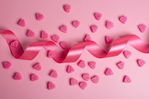 Coeurs roses sur fond rose pastel avec ruban. fond romantique pour la saint-valentin