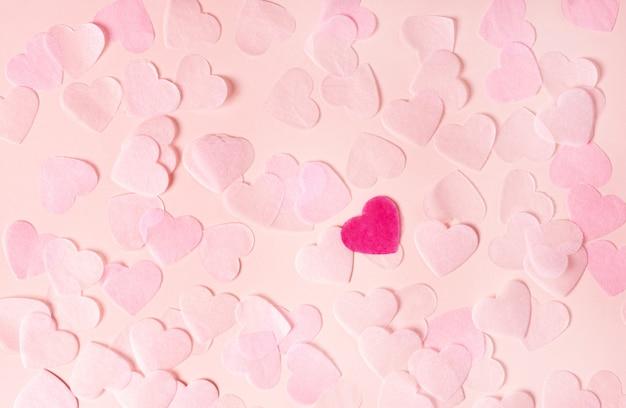 Coeurs roses en papier sur une surface rose