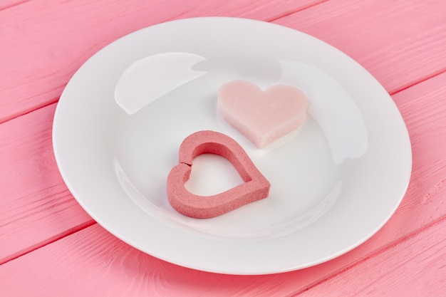 Coeurs roses sur plaque blanche. coeurs de saint valentin et assiette en porcelaine sur fond en bois rose. joyeuses fêtes de la saint-valentin.