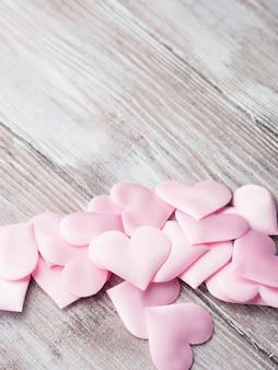 Coeurs roses sur une table en bois texturée