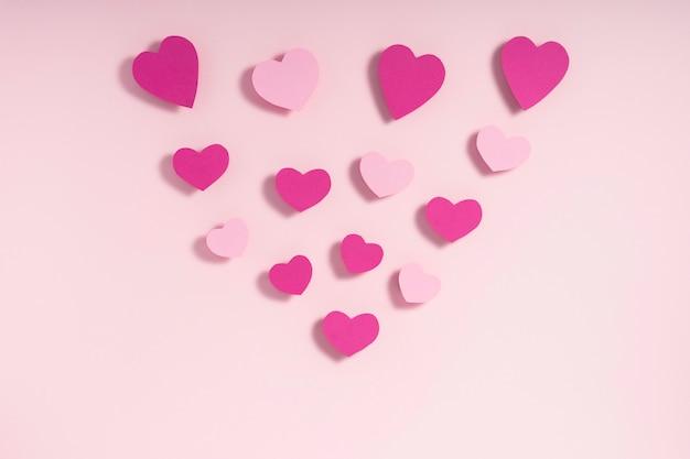 Coeurs roses et violets sur une surface rose pastel
