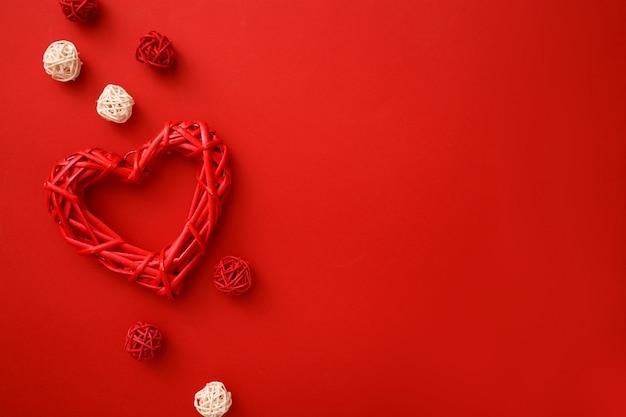 Coeurs en rotin avec décoration sur plat rouge. célébration de la saint-valentin.