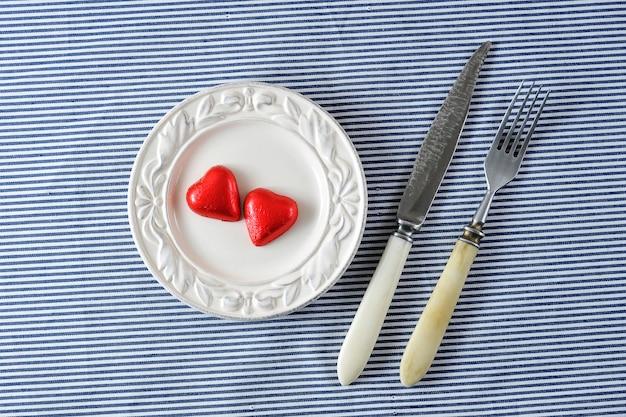 Coeurs rouges sur une assiette et un couteau avec une fourchette