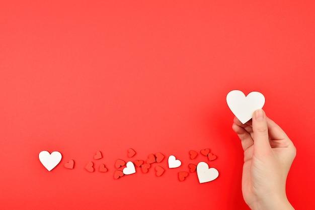 Coeurs rouges et blancs sur fond rouge. femme tenant un coeur blanc. copiez l'espace.
