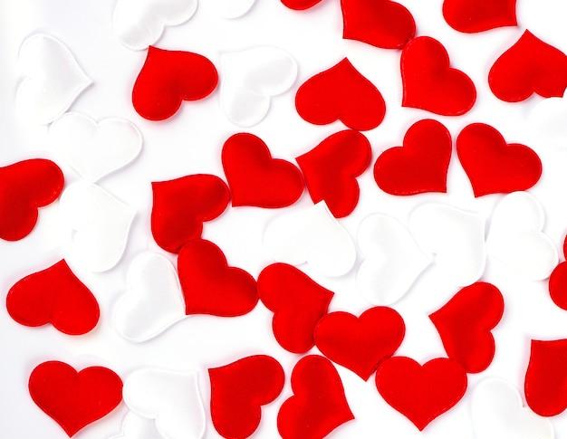 Coeurs rouges et blancs sur fond de tissu texturé blanc