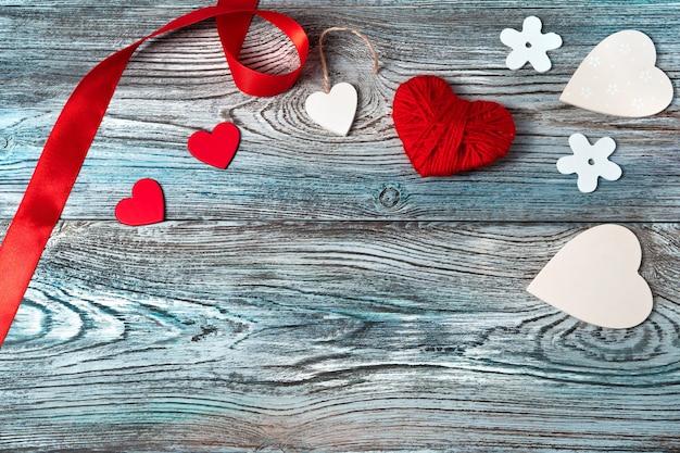 Coeurs rouges et blancs et ruban sur un fond gris-bleu en bois.