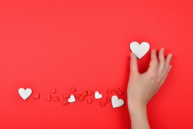 Coeurs rouges et blancs sur une surface rouge woman holding white heart copy space