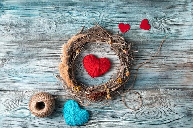 Coeurs rouges et bleus et une couronne de branches naturelles et d'herbe sèche sur un fond en bois gris-bleu.