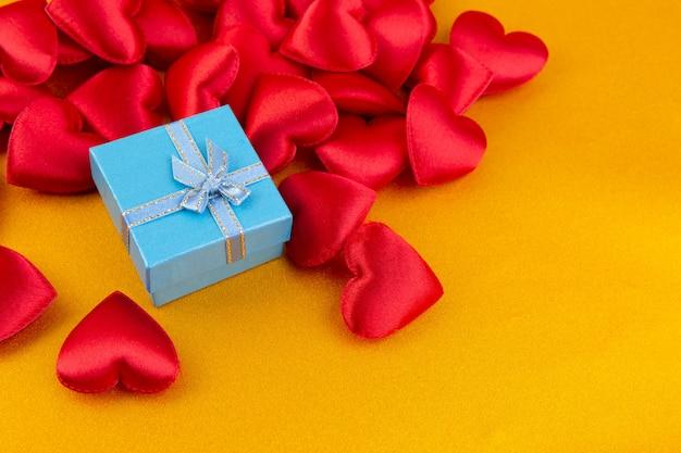 Coeurs rouges avec boîte-cadeau sur or de couleur paillettes, fond de saint valentin
