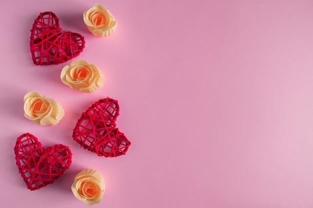 Coeurs rouges et boutons de rose orange sur rose