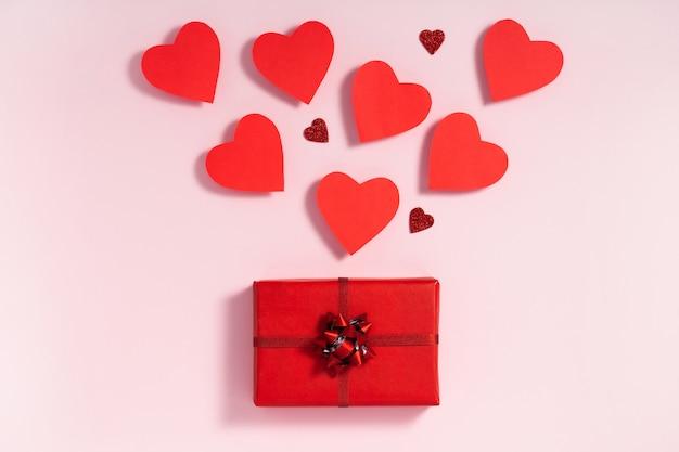Coeurs rouges et coffret cadeau sur fond rose pastel