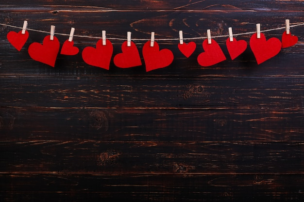 Coeurs rouges sur une corde avec des pinces à linge, sur un fond en bois noir. place pour le texte, espace de copie.