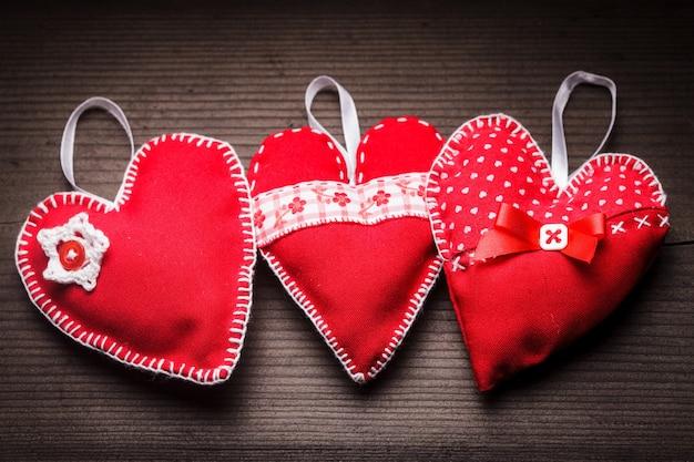 Coeurs rouges cousus à la main sur fond de bois