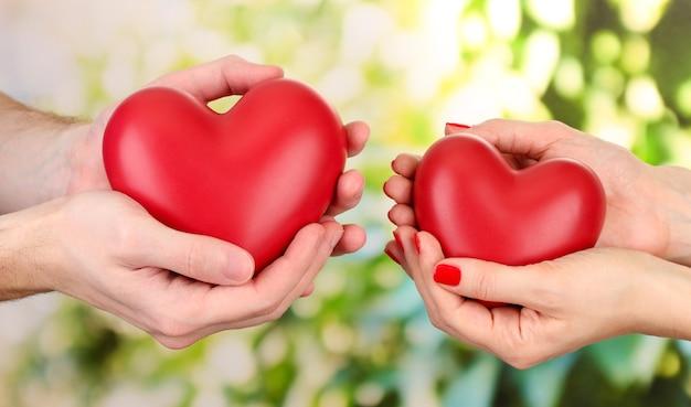 Coeurs rouges dans les mains de la femme et de l'homme, sur le vert