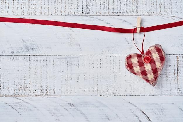 Coeurs rouges faits à la main sur ruban rouge devant un mur en bois. carte de voeux saint valentin. vue de dessus.