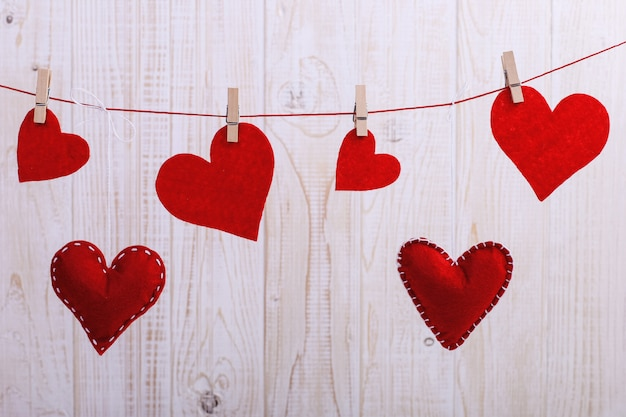 Coeurs rouges en feutre fait main suspendus à une corde avec une épingle