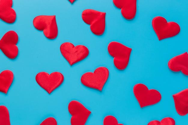 Coeurs rouges sur fond bleu plat.