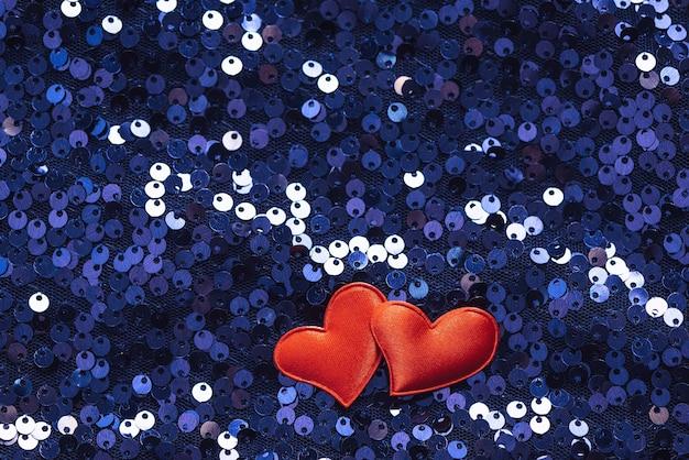 Coeurs rouges sur fond brillant de tissu brodé de paillettes