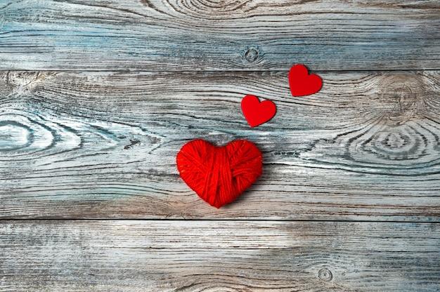 Coeurs rouges sur fond gris-bleu en bois.