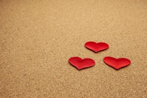 Coeurs rouges sur fond de liège.