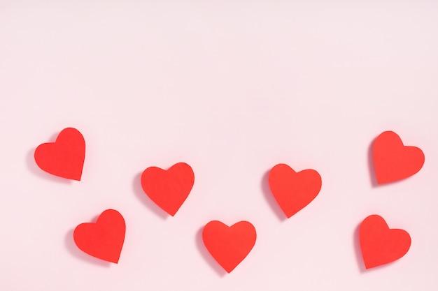 Coeurs rouges sur fond de papier rose
