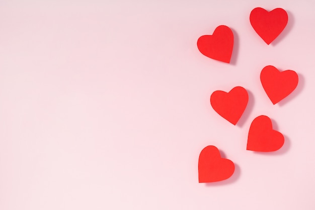 Coeurs rouges sur fond rose pastel