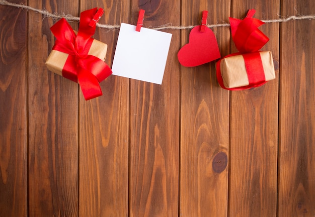 Coeurs rouges en papier et un cadeau en papier kraft sur bois