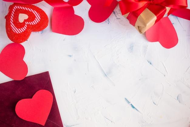 Coeurs rouges en papier et un cadeau en papier kraft sur une lumière