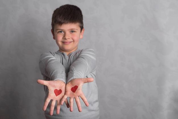 Coeurs rouges sur les paumes du bébé. le dessin aux couleurs rouges sur les bras du garçon est en gros plan. le bébé sur un fond gris montre des paumes avec un modèle des coeurs