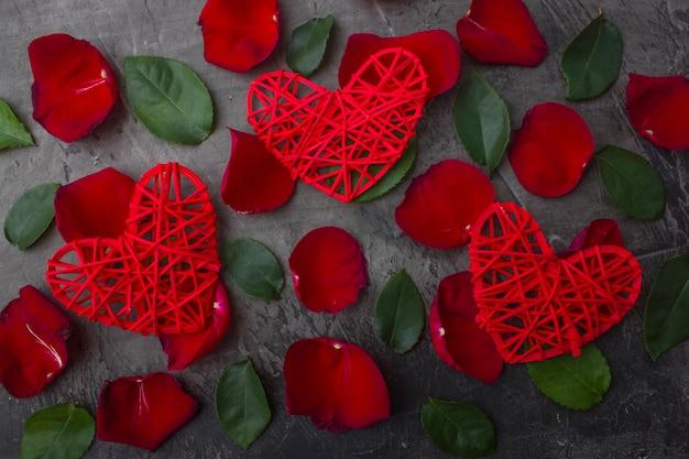 Coeurs rouges sur pétales de rose et feuilles vertes