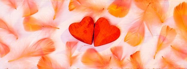 Coeurs rouges avec des plumes orange sur une planche de bois