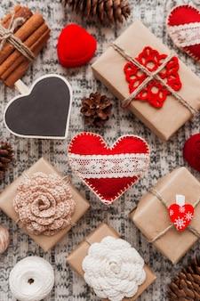 Coeurs de la saint-valentin, cadeaux en papier kraft avec fleurs au crochet, pommes de pin, écrin rouge.