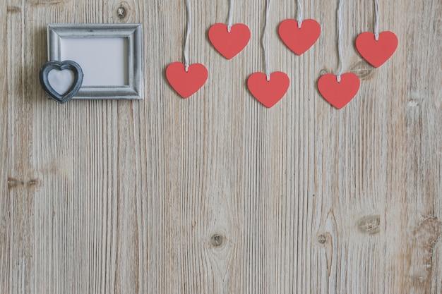 Coeurs suspendus sur une corde et un cadre blanc