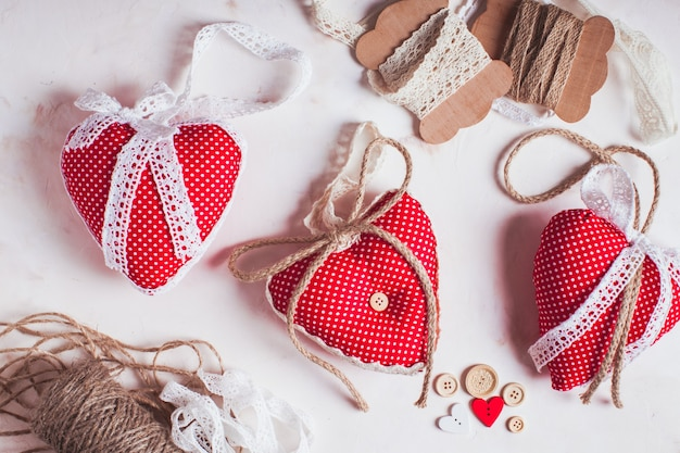 Des coeurs en textile à pois rouges sur la table. processus de couture et de conception