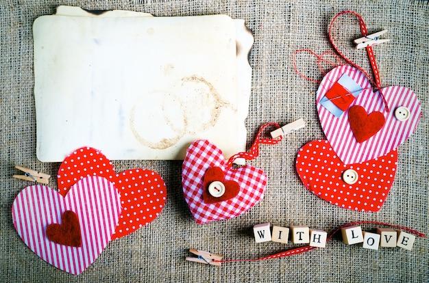 Coeurs en textile à pois rouges sur toile de jute. espace libre pour votre texte.
