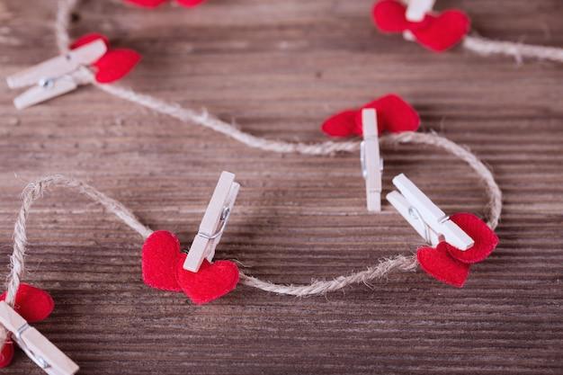 Coeurs en textile rouge reliés par une pince à linge. concept de l'amour