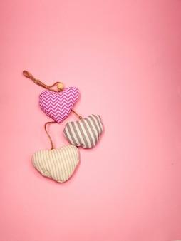 Des coeurs en tissu doux volent sur un fond de couleur rose tendre, copiez l'espace. concept de la saint-valentin pour la conception.