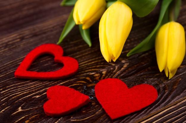Coeurs en tissu près des tulipes. fleurs et coeurs sur bois. impressionnez une fille avec un cadeau. symboles de salutation.